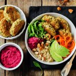 Quinoa Beet Hummus Falafel Bowl on a wood background. toning. selective focus